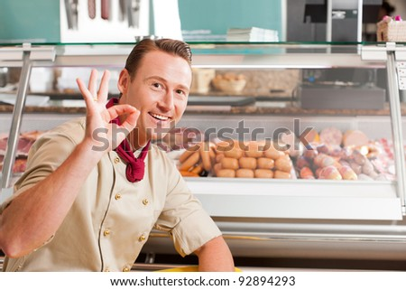 Happy butcher showing okay sign with variety of fresh meat in background