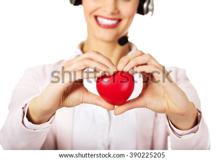 Happy call center woman holding heart toy - stock photo
