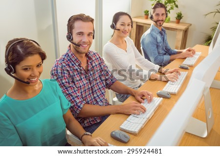 Happy call centre team working together and looking at the camera - stock photo