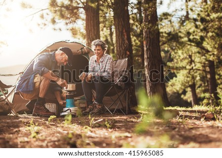 Happy campers outdoors in the wilderness and making coffee on a stove. Senior couple on a camping holiday. - stock photo