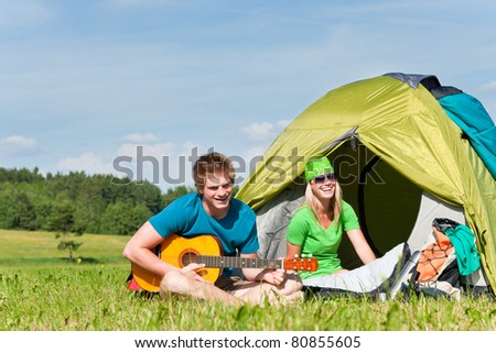 Happy camping couple sitting by tent play guitar sunny countryside - stock photo