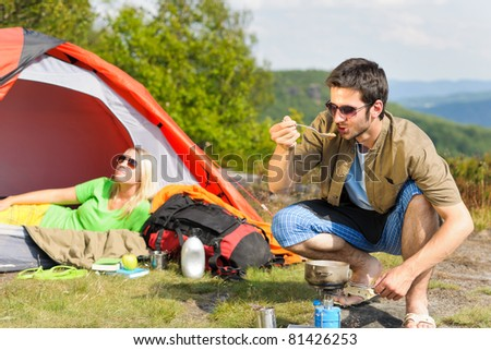 Happy camping couple with tent backpack cooking in sunny countryside - stock photo