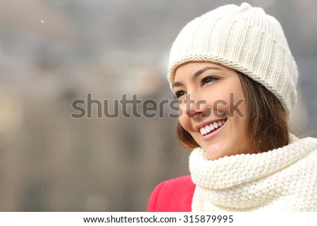 Happy candid girl with white teeth and perfect smile warmly clothed in winter - stock photo