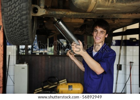 happy car mechanic working at the car  repair  shop - stock photo