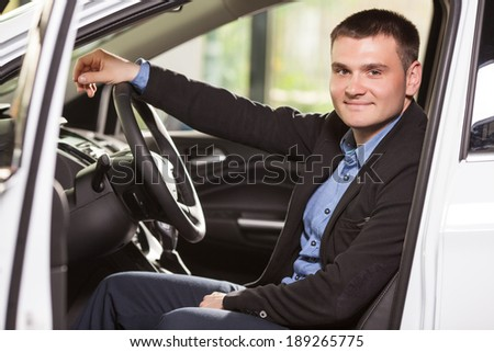 Happy car owner at the dealership. Handsome young men sitting at front seat of the car looking at camera - stock photo
