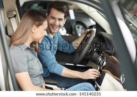 Happy car owners. Beautiful young couple sitting at the front seats of their new car - stock photo