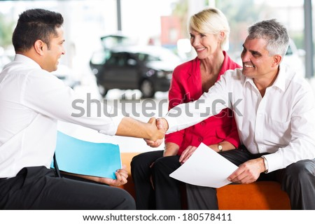 happy car salesman handshaking with senior buyer - stock photo