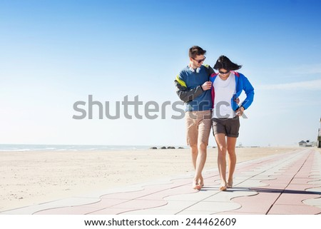 Happy carefree barefoot young couple walking arm in arm on a seafront boardwalk alongside the golden sea sand on a hot summer day smiling and chatting, with copyspace - stock photo
