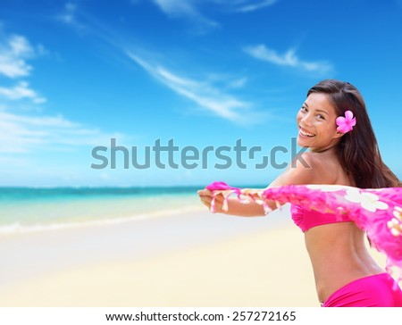 Happy carefree hawaiian woman relaxing on beach. Perfect tropical white sand beach background woman posing free with pink scarf in the wind during her Hawaii summer vacations. - stock photo