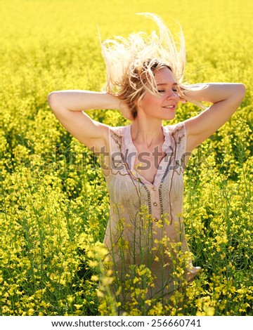 Happy carefree summer girl in rape field. Cheerful young woman joyful in spring, smiling with arms raised up, and closed eyes - stock photo