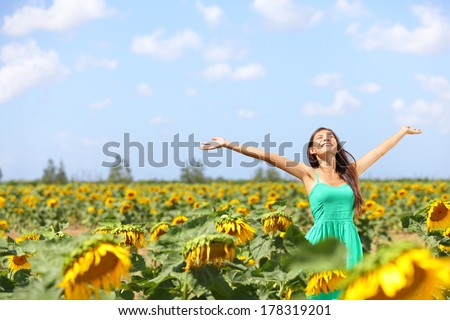 Happy carefree summer girl in sunflower field in spring. Cheerful multiracial Asian Caucasian young woman joyful, smiling with arms raised up. - stock photo