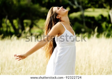 happy carefree vitality freedom girl stands with her hands outstretched embracing nature and a warm summer day
