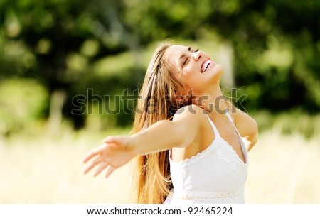 happy carefree vitality freedom girl stands with her hands outstretched embracing nature and a warm summer day - stock photo