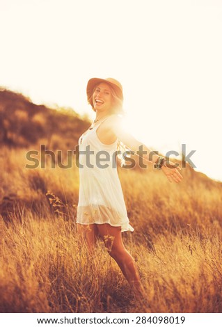 Happy Carefree Young Woman Outdoors. Warm sunset colors. - stock photo
