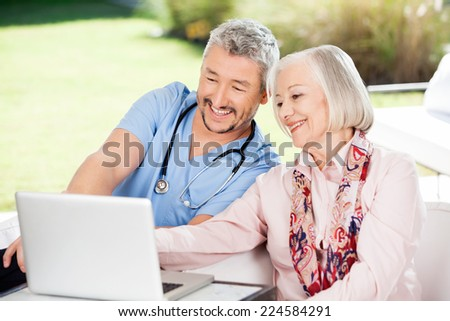 Happy caretaker and senior woman using laptop at nursing home porch - stock photo