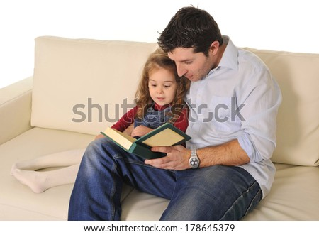 Happy caring Father and sweet  little daughter reading book on couch together - stock photo