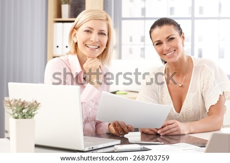 Happy casual blonde and brunette businesswomen at office working in front of laptop computer, checking business report papers, smiling, looking at camera.