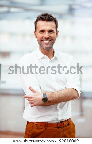 Happy casual businessman looking at camera against blurred background - stock photo