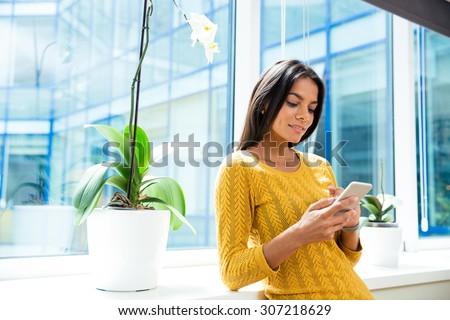Happy casual businesswoman using smartphone in office near window - stock photo