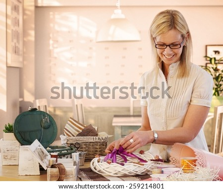 Happy casual caucasian blonde mid adult housewife making valentine day wreath at home. Smiling, wearing glasses, standing at table, do it yourself, gift, present. - stock photo
