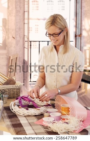 Happy casual caucasian blonde mid adult lady making valentine day wreath at home. Smiling, wearing glasses, standing at table, do it yourself, gift, present. - stock photo