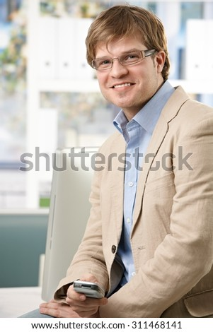 Happy casual caucasian businessman with mobile phone at office in hand. Wearing glasses and suit, looking at camera.