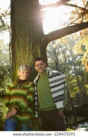 Happy casual caucasian couple in fall forest outdoor low angle. Smiling, standing, looking at camera, sun flare. - stock photo