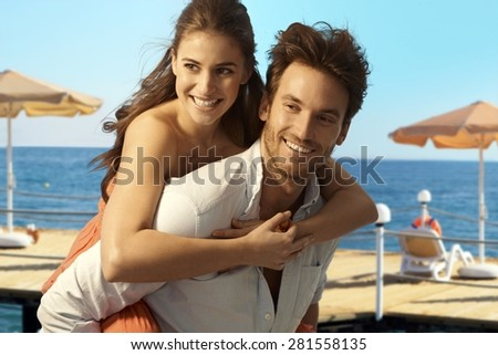 Happy casual caucasian couple playing piggyback at seaside summer holiday beach. Smiling, having fun. - stock photo