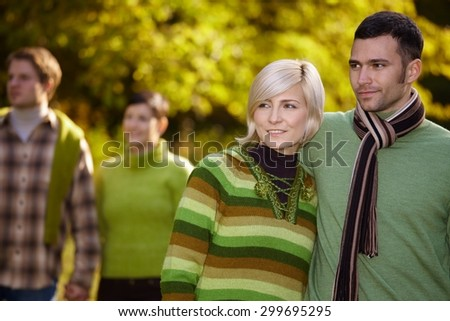 Happy casual caucasian couple with friends walking outdoor. Smiling, wearing warm clothes at autumn. - stock photo