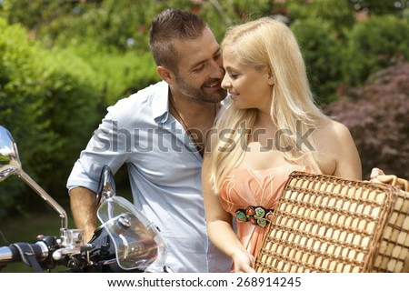 Happy casual caucasian couple with scooter and picnic basket. Blonde smiling woman with handsome man, outdoor. - stock photo