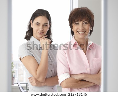 Happy casual caucasian female business office workers, standing, smiling, looking at camera, hand under chin, arms crossed. - stock photo