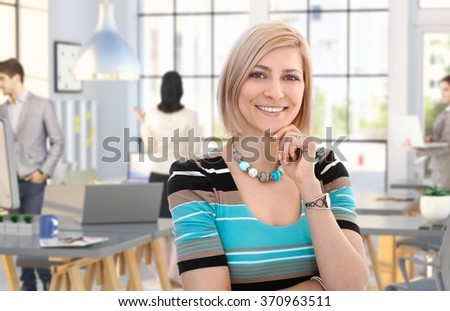 Happy casual caucasian woman standing at office, smiling, people working in background. - stock photo