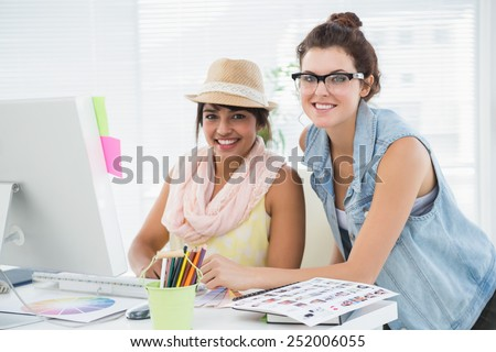 Happy casual colleagues working together in the office - stock photo