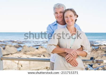 Happy casual couple hugging by the coast on a sunny day