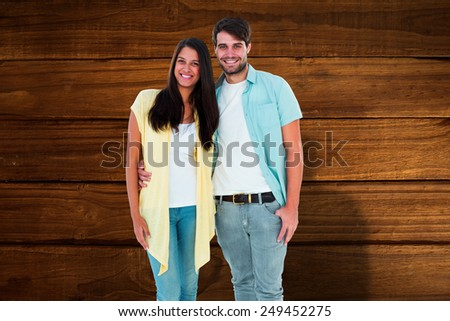Happy casual couple smiling at camera against overhead of wooden planks - stock photo
