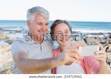 Happy casual couple taking a selfie by the coast on a sunny day - stock photo