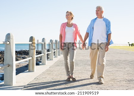 Happy casual couple walking by the coast on a sunny day - stock photo