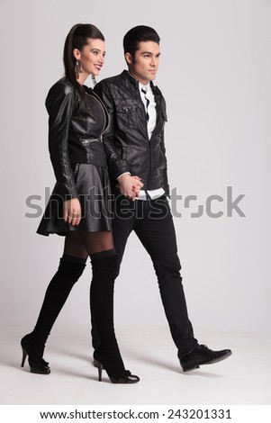 Happy casual couple walking together holding hands, on grey studio background. - stock photo