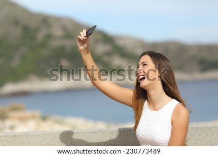 Happy casual elegant girl photographing a selfie on the beach enjoying holidays and laughing - stock photo