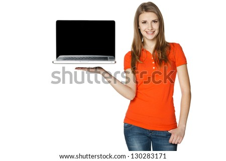Happy casual female showing a laptop screen, isolated over a white background - stock photo