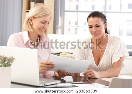 Happy casual female workers at business office working in front of laptop computer checking report papers, smiling.