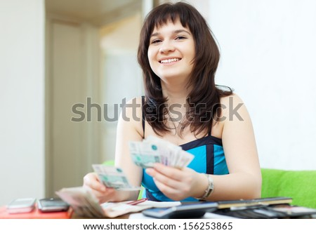 happy casual girl calculates the family budget  with money and documents  in home interior