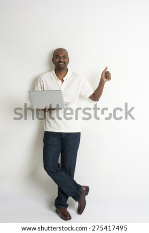 happy casual indian male with a laptop and thumbs up - stock photo
