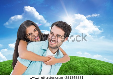 Happy casual man giving pretty girlfriend piggy back against green hill under blue sky - stock photo