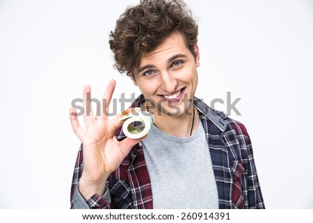 Happy casual man holding money over gray background - stock photo