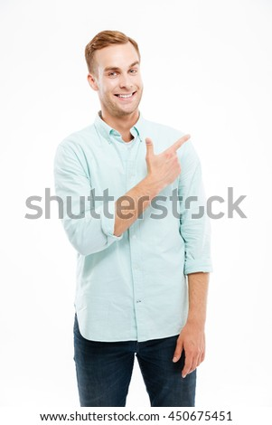 Happy casual man pointing finger away at copyspace isolated on a white background - stock photo