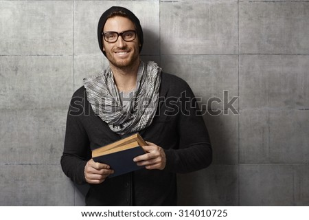 Happy casual man reading book, leaning against grey wall.