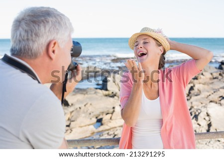 Happy casual man taking a photo of partner by the sea on a sunny day