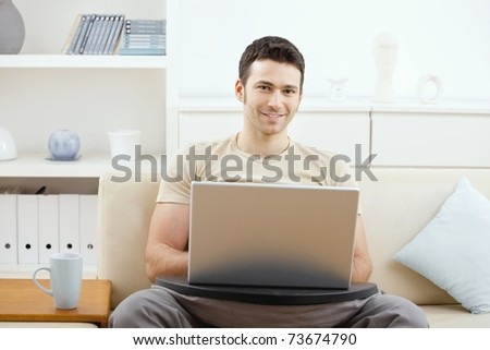 Happy casual man using laptop computer at home, sitting on couch, looking at camera, smiling.? - stock photo