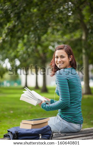 Happy casual student sitting on bench reading on campus at college - stock photo